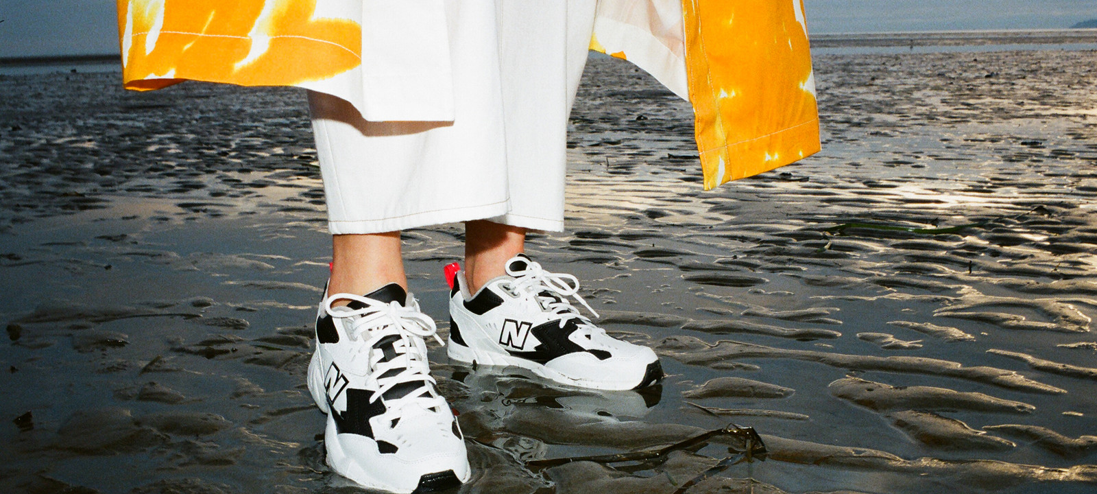 New Balance Sneakers Sneaker Spring Summer 2019 608v1 Black White Dries Van Noten Orange Coat White Pants Editorial Beach Sand Golden Hour