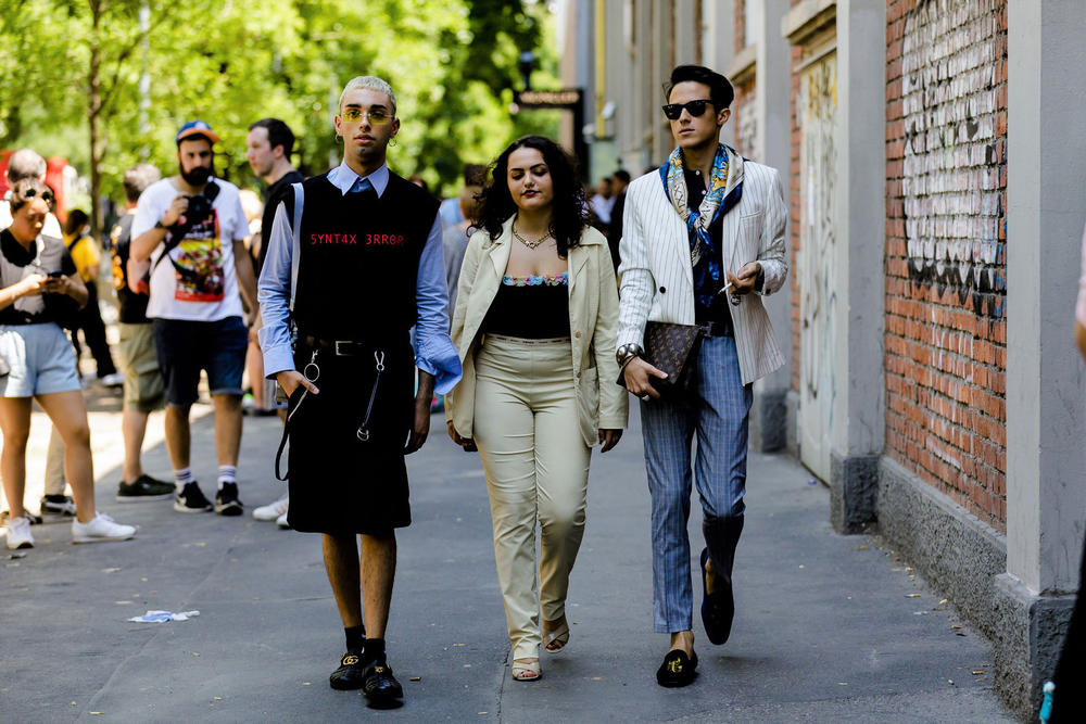 milan fashion week street style spring summer 2019 syntax error black vest louis vuitton clutch bag hermes belt gucci slippers blue shirt sweater vest shorts black