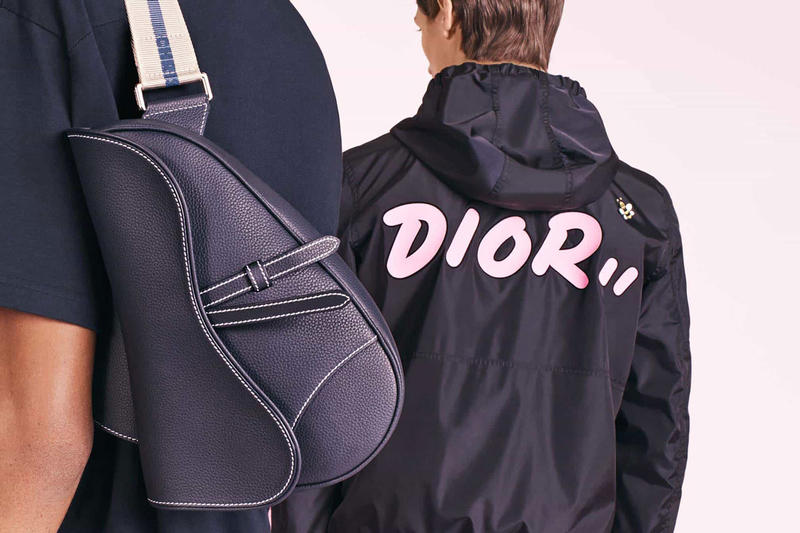 dior menswear kim jones kaws bee collaboration capsule collection release date body bag leather saddle logo track jacket print strap branding blue navy tee shirt