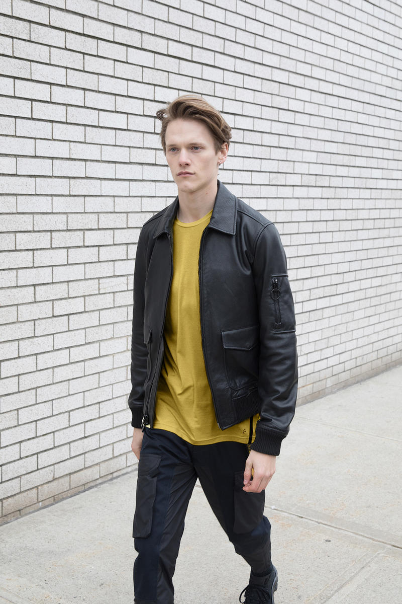 the arrivals mountain wear parkas bombers unisex tees leather jackets yellow shirt brick wall