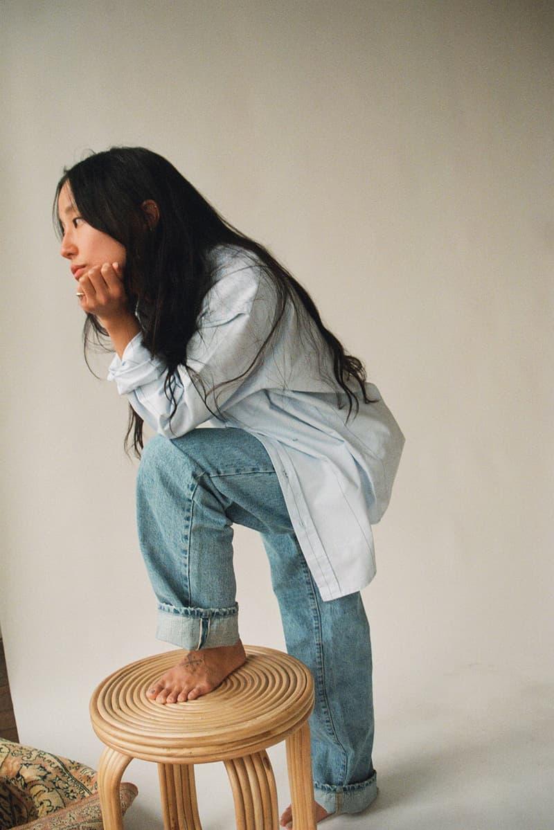 noah international womens day editorial donation charity kula project brianna capozzi red long sleeve denim jeans black boots stripe shirt