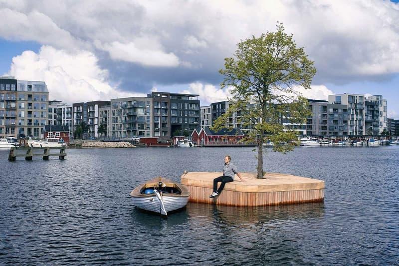 """小さな無人島が公共のスペースとして活用するコペンハーゲンの一風変わった取り組みをご紹介 ヨーロッパでも有数の観光地であるデンマークの首都コペンハーゲンにてユニークな試みがスタートしている。  その名も""""Copenhagen Islands""""は、誰もが自由に使える多目的なパブリックスペースとして小型の無人島をコペンハーゲン湾に浮かべるプロジェクトである。  オーストラリアの建築家、Marshall Blecher(マーシャル・ブレッヘル)とデンマークのデザインスタジオが共同で手掛けた20㎡の小さな人工の島は、ボート作りに使用される伝統的な技術を用いて、サスティナブルな地元の木材から制作されており、中央には1本のシナノキが植えられている。  現在、試験運用的にCPH-Ø1と名付けられた1つの島が浮かべられているが、カヤック乗りや遠泳中の人たちの休憩スポット、日光浴や釣り、小規模なイベントなどに利用されているという。将来的には、CPH-Ø2、Ø3と続く形で9つの島に拡大し、サウナや庭園をはじめ、ボートに乗りながらドライブスルーのように利用できるカフェを水上に展開する計画がある。また、浮遊するこれらの島々は移動させることが可能であり、複数集まることでその用途も多様化する。先行分のCPH-Ø1も今年いっぱいは季節毎にロケーションを変えながら運用される。  先述のように、この無人島は公共の場として自由に利用できるので、ヨーロッパを訪れる機会があれば、コペンハーゲン湾での水上BBQやキャンプを楽しんでみてはいかがだろうか。"""