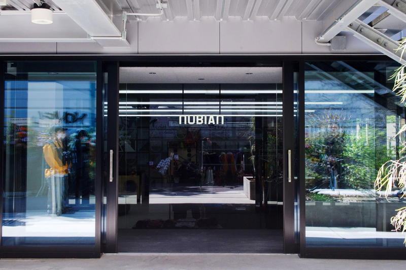"""移転によりパワーアップを遂げた『NUBIAN HARAJUKU』の店内を初公開 旧店舗の約5倍にも拡大した新店舗はオンライン上にはないリアルな体験そのものをデザインした洗練された空間に ラグジュアリーストリートの代表格から高感度な国外のヘッズたちが目をつけ出しているアップカミングレーベルまで、""""行き届いた""""セレクトで信頼を集め、国内外から客足の絶えない『NUBIAN(ヌビアン)』が、原宿店を移転リニューアル。本稿では、一新された店内の様子を世界初公開しよう。  裏原宿から東郷神社の裏手、竹下通りの脇道へとスペースを移した『NUBIAN HARAJUKU』は、『TRUNK(STORE)』や『BEAMS JAPAN』を手がけた経歴を持つ「トラフ建築事務所」に内装協力を依頼し、敷地面積は旧店舗の約5倍に値する90平米にも拡大。左右非対称に広がるコの字型のスペースは、特定のブランドがイベント的に使うポップアップエリア、スケルトン天井の中央エリア、店内奥の高額商品を扱うエリアの3セクションに分割され、ひとつの大きな空間でありながら、高低差や内装材、照明などでエリア毎に個性を持たせている。また、色彩、形状豊かなプロダクトが雑然と見えないよう、店内には随所に幾何学的なインテリアが配置され、そのうちのいくつかはカラフルなフレームで『NUBIAN』の文字を模り、モノトーンな空間にプレイフルな要素をプラス。さらに、中央には純国産高級サウンドシステムを提供する「田口音響研究所」の技術が搭載されたウーファー内蔵のカウンターと高音質スピーカーが鎮座し、ポップアップやDJイベントなど、様々な使い方を許容する""""余白""""のあるスペースを目指したとのことだ。  オンラインが台頭する中、実店舗において商品と出会う体験そのものをデザインしたいと考えて設計された新生『NUBIAN HARAJUKU』。〈Maison Margiela(メゾン マルジェラ)〉や〈ACRONYM(アクロニウム)〉など、ハイエンドなブランドもストックされたことにより、セレクトショップとしての進化を感じさせるのみならず、今後はよりパワーアップしたプロジェクトが展開されることになるだろう。  『NUBIAN HARAJUKU』の店内の様子は、上の@フォトギャラリーから。あわせて、『NUBIAN』の主要メンバーである若手敏腕バイヤー幅田将平のストリートスナップもプレイバックしてみてはいかがだろうか。"""
