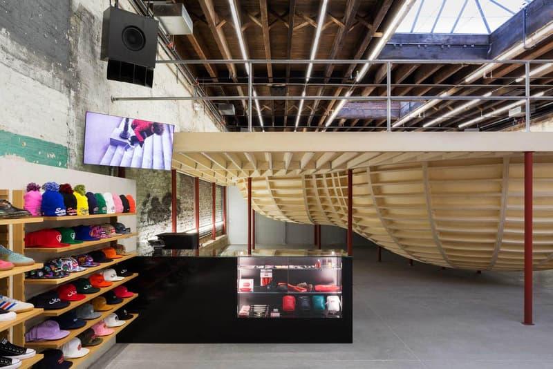 """Supreme のブルックリン店の内装デザインを隅々まで撮影したフォトセットが到着 『Supreme Brooklyn』の前は配送用トラックの収納スペースだったとのこと 〈Supreme(シュプリーム)〉は昨年10月、ニューヨーク・ブルックリン地区に新ストアをオープン。実はこの場所、ストリートウェアの雄のためにNeil Logan(ニール・ローガン)とMinji Kim(ミンジ・キム)の2人が改装する前は、2,938㎡を要する配送用トラックの収納スペースだったのだ。  天井が高く、しっくりを剥がした2m超えのブロック壁に囲まれた空間は、隆起したグラインドレール付きのメタルベンチを設置することで、質素ながらもどこかインダストリアルな雰囲気が漂う。また、店内の奥には『Supreme Brooklyn』の最大の特徴である木製のスケートボウルが鎮座。『ArchDaily』はこのアイコンについて、「バルト海産の樺の木でできたベニヤ板を100%使用したこのボウルは、アートコレクティブのSimparchがシカゴで製造して、ここまで運び、インストールしたものです」と説明している。  また、このジオメトリックなボウルの裏には、カーテンで覆われた更衣室が2部屋隠れており、スケートクリップを流している店頭の液晶も背面には鏡を設置。そして、入り口の壁裏を覆い尽くすスケートデッキとアートワークも見逃せないポイントだろう。  『Supreme Brooklyn』の内装を隅々まで撮影したフォトセットは、上のフォトギャラリーからどうぞ。  ちなみに、〈Sup〉が2018年春夏コレクション内の""""Alphabet""""シリーズの販売を突如中止した理由はご存知?"""