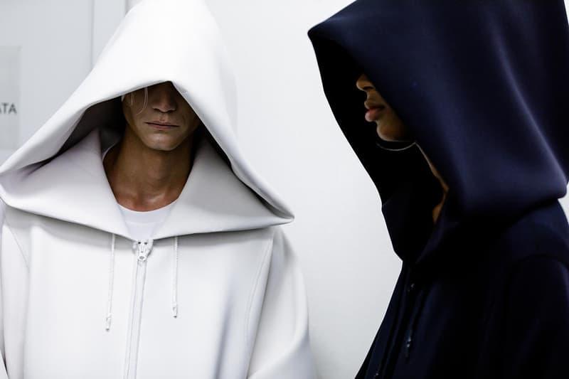 """丸龍文人の帰還は、2019年春夏シーズン最大のトピックのひとつだった。〈COMME des GARÇONS(コム デ ギャルソン)〉退社から約2年の時を経て、同氏は自身の名を冠した〈FUMITO GANRYU(フミト ガンリュー)〉を「Pitti Uomo(ピッティ ウォモ)」の""""Designer Project""""で発表。幸運にも、『HYPEBEAST』はこの新たな船出となるランウェイの舞台裏に潜入する機会を得ることができた。  1stコレクションに言及する前に、〈GANRYU〉の時代を振り返ってみたい。シャツ、デニム、テーラードジャケットなど、ベースとなるカジュアルウェアは決して新鮮味を感じるものではない。だが、丸龍氏の手にかかれば、それらの洋服はモードに寄っていくのではなく、文字通り""""昇華""""されてしまうのだ。かつて『Union(ユニオン)』のChris Gibbs(クリス・ギブス)も「COMME des GARÇONSファミリーの中で最も完璧なブランドだ。なぜなら、GANRYUはストリートウェア、ワークウェア、ハイファッションを融合しているからである」と『BoF』の中で同氏のクリエイションを手放しに賞賛。それだけ、〈GANRYU〉はどこよりも早く、ランウェイからストリートにリーチしていたのだ。  〈FUMITO GANRYU〉のデビューコレクションは、会場に水の逆光写真が飾られた空間でお披露目を迎えた。ランウェイでは極限までクリーンに仕立てられたスポーツウェアが随所で登場し、カトリックの衣装を彷彿とさせるオーバーサイズのフーディや半透明のクリアベルトを採用したサンダルがキーピースに。そのシルエット美には誰しもが「シーンに丸龍文人が帰ってきた」と感じたことだろう。  〈FUMITO GANRYU〉初のコレクションの細部に迫るバックステージフォトは、上のフォトギャラリーから。取扱店舗などの詳細は、@fumitoganryuなどを含め、ブランドからのアップデートを待とう。  あわせて、先日閉幕したロンドンファッションウィーク・メンズ期間中に敢行したストリートスナップもお見逃しなく。"""