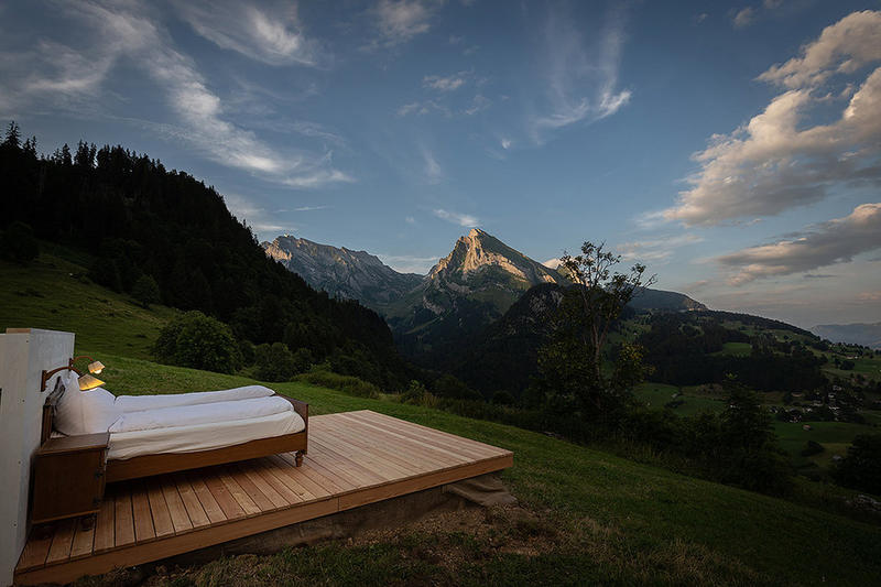 """大自然をそのまま体感できる屋根も壁もない青空ホテル Zero Real Estate お盆を目前に控え、早くもレジャー気分に浸っている紳士淑女のみなさんに、本稿では世にも奇妙なホテルをご紹介しよう。 『Zero Real Estate』は、トッゲンブルク地方のスイスアルプスに位置するポップアップホテルであるが、このホテルほど大自然を肌で体感できるホテルは存在しないのではないだろうか。それもそのはず、なぜなら『Zero Real Estate』には壁も屋根もなく、美しい緑が生い茂る山の斜面にダブルベッドが1台置いてあるだけだからである。この色々な意味で""""特別""""な空間の目の前には、クルフィルシュテン山脈やシュヴェンディー湖、ライン渓谷が広がり、朝は太陽の日差しとともに目を覚まし、まるでハイジのような気分を味わうことができるだろう。「折角予約したのに悪天候だった場合は?」と不安に思う方もご安心を。そういった場合に備えて、プランにはバックアップルームが含まれているのだ。  『Zero Real Estate』の宿泊費は、朝食、駐車場、専用の執事がついて約33,000円。すでに一部プランは2018年の予約が埋まってしまっているが、気になる方はこちらから全貌をチェックしてみてはいかがだろうか。  インドネシアの秘島に建つ地中海ムード溢れるオーシャンビューヴィラや、バリ島のマウンテンサイドに佇むオアシス『Chameleon Villa』など、その他の極上リゾートもあわせてチェック。"""